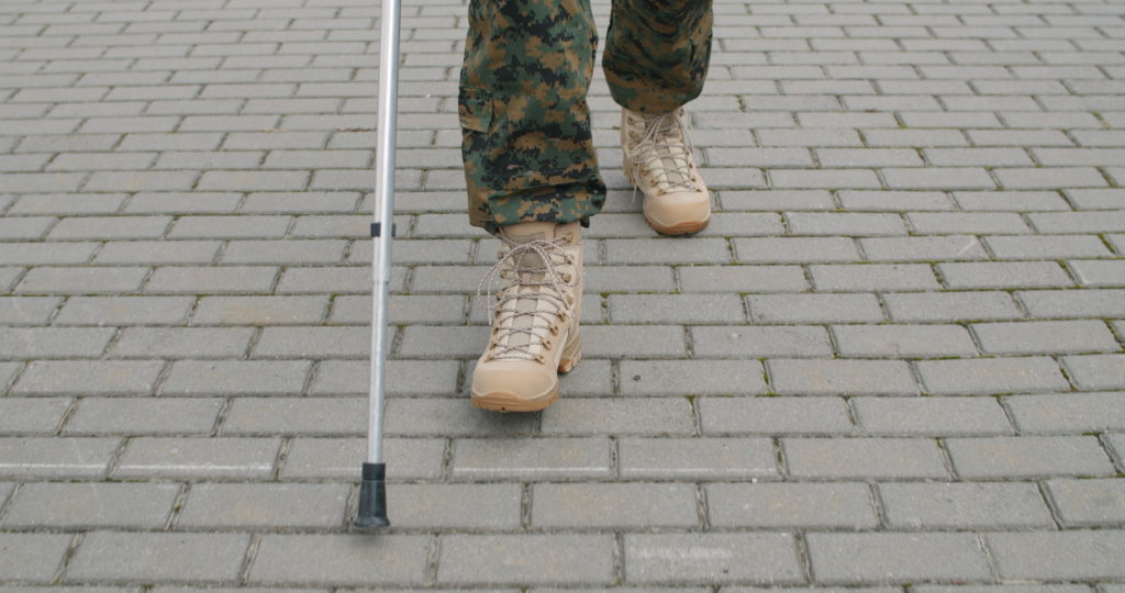 Crop view of veteran walking with crutch after discussion with a VA Disability Lawyer