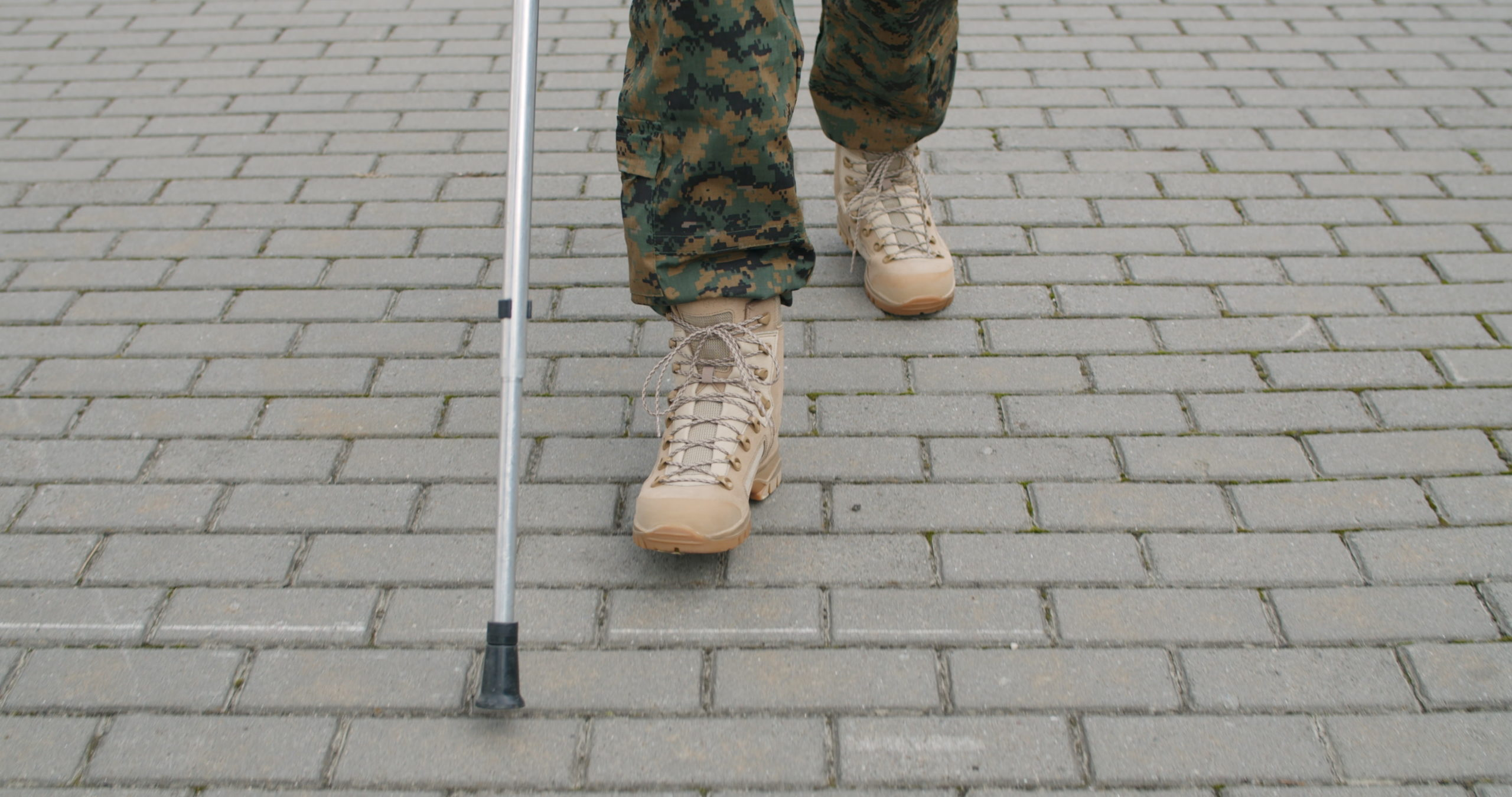 Crop view of veteran walking with crutch after discussion with a VA disability attorney.