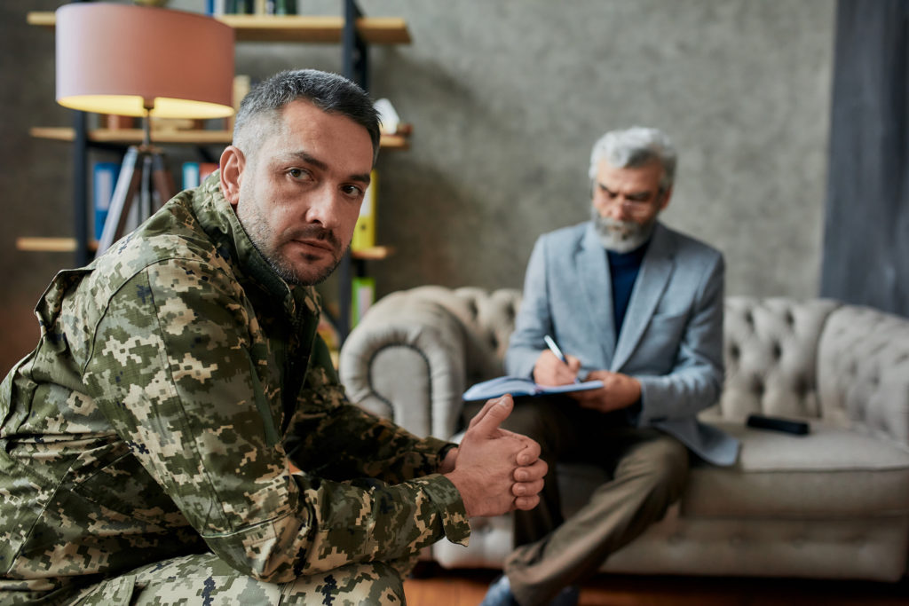 Middle aged military man looking aside during therapy session while discussing personality disorders disability benefits